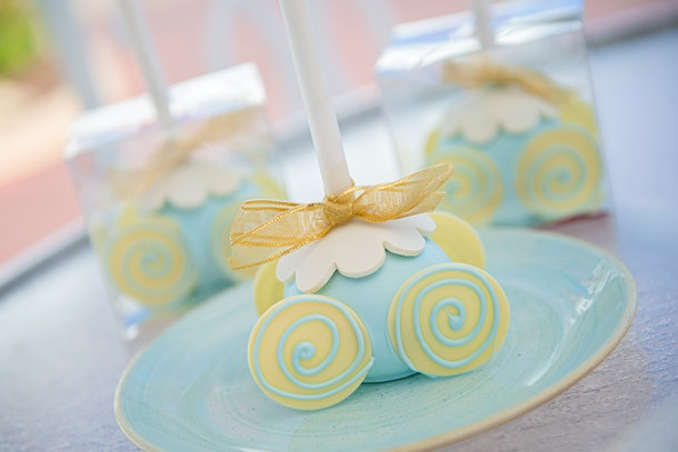 A blue and yellow 'Cinderella' carriage cake pop sits on a blue plate at Disney.