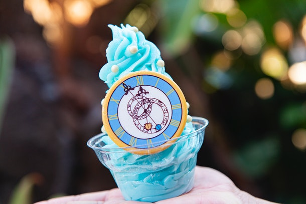A woman holds up a blue, sparkly Cinderella Dole Whip with a white chocolate clock at Disney.