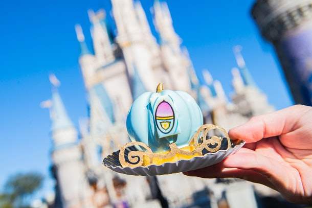 A woman holds up a 'Cinderella' treat made to look like her carriage in front of the castle at Disney World.