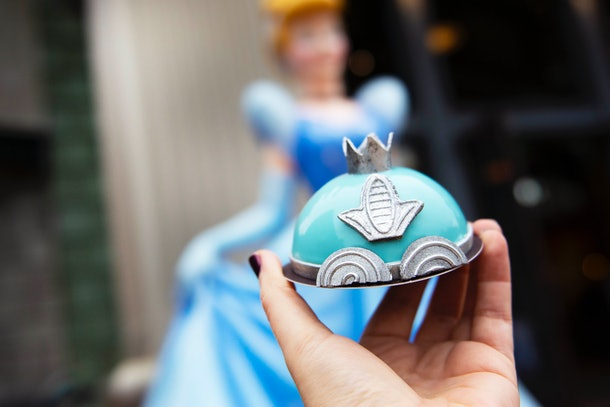 A woman holds up the Cinderella Mini Dome Cake that's available at Disney Springs, in front of a Cinderella statue.
