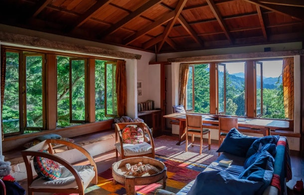 The Lost Coast Tower listed on Airbnb has a colorful living room with windows all around, overlooking nature.