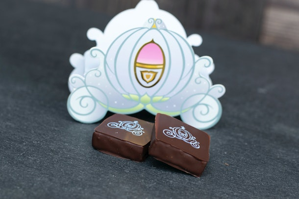 Two pieces of chocolate sit on the table in front of a chocolate box that's shaped like Cinderella's carriage at Disney.