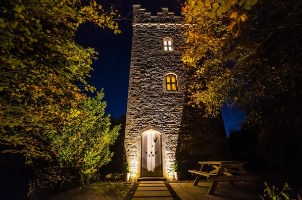 A castle tower in Ireland that is listed on Airbnb is lit up with lights at night.
