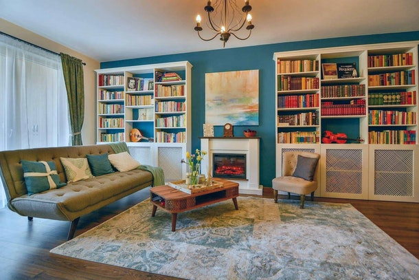 A living room within an Airbnb apartment has charming blue walls and books.