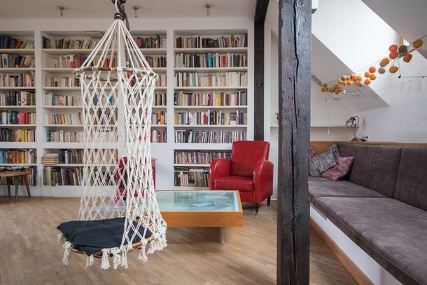 A swing hangs in the middle of a living room on Airbnb with bookshelf walls, just like the library in 'Beauty and the Beast.'