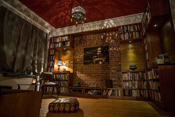 A chandelier lights up an elegant library, like the one from 'Beauty and the Beast,' within an Airbnb home.