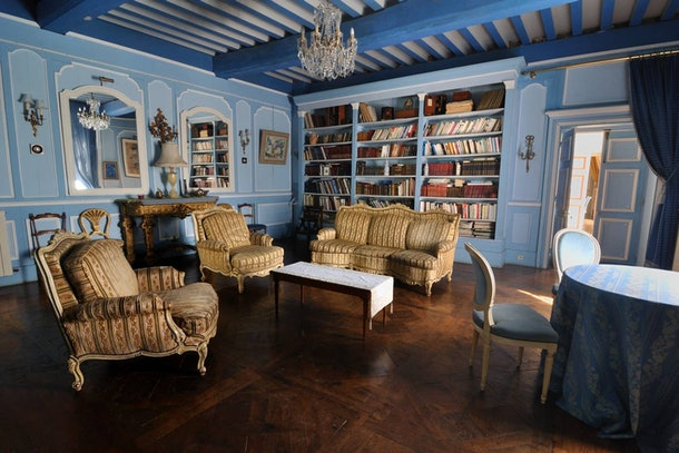 An elegant blue room in an Airbnb castle has books on the shelves, just like the library in 'Beauty and the Beast.'