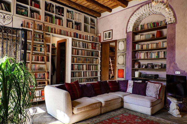 Books fill the bookshelves in the walls, just like the library in 'Beauty and the Beast,' in this charming living room that's listed on Airbnb.