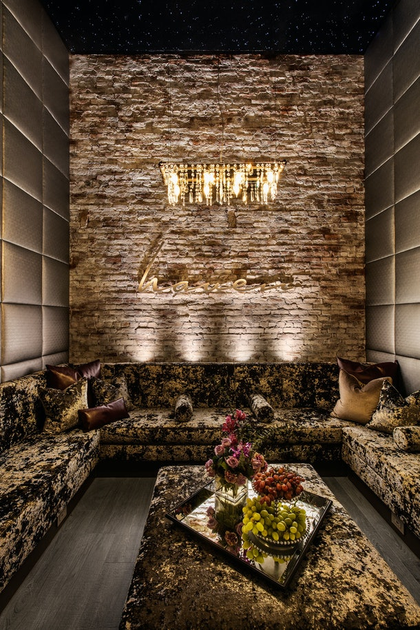 The interior of Haven Spa NYC features a luxurious couch, chandelier, and stone wall.
