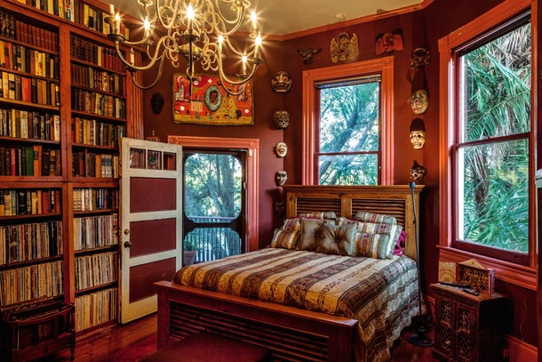 A bedroom in a New Orleans Airbnb has books on the shelves, just like the library from 'Beauty and the Beast.'