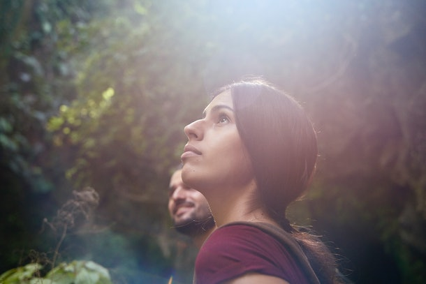 Young woman and young man looking at sun in forest