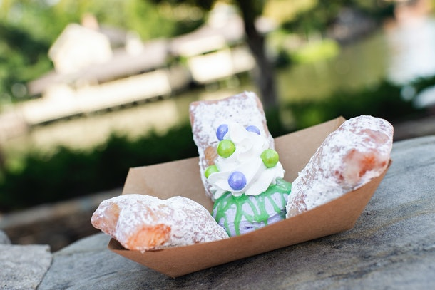 Three beignets covered in powdered sugar sit on a rock at Disney for the Disney Villains After Hours event.