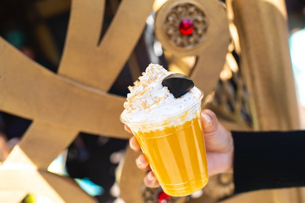 A woman holds up a yellow slush drink inspired by Jafar from 'Aladdin' for the Disney Villains After Hours event with a edible diamond on top.