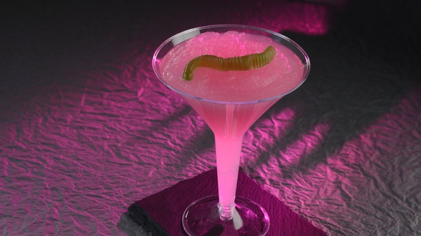 A pink mocktail inspired by Hades from 'Hercules' sits on a table at Disney for the Disney Villains After Hours event with a gummy worm in it.