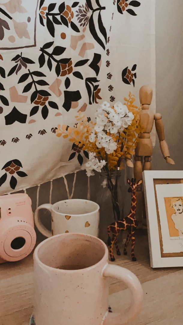 A mug, flowers, and a framed print of Marilyn Monroe sit on a desk on a sunny day.