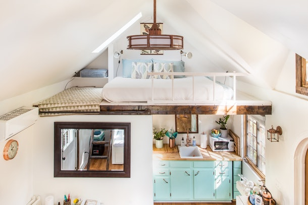 A tiny home is designed to look very cozy with teal cabinets, lots of natural sunlight, and a lofted bed.