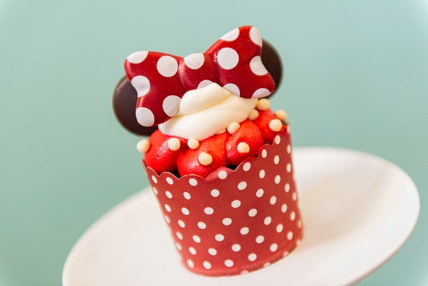 A Minnie Mouse cupcake with chocolate ears and red and white icing sits on the table for Valentine's Day at Disney.