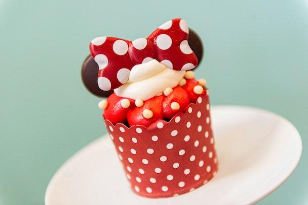 Un cupcake Minnie Mouse avec des oreilles en chocolat et du glaçage rouge et blanc est posé sur la table pour la Saint Valentin à Disney.