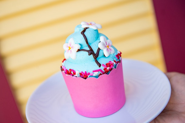 A cherry blossom-themed cupcake with blue icing sits on a plate at Disney for Valentine's Day.