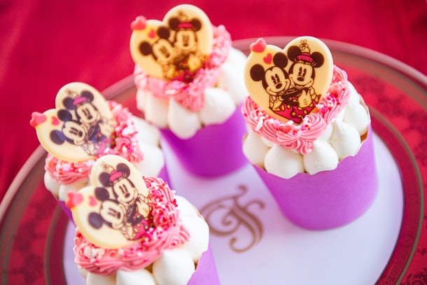 Mickey and Minnie-themed cupcakes sit on a plate for Valentine's Day at Disney.