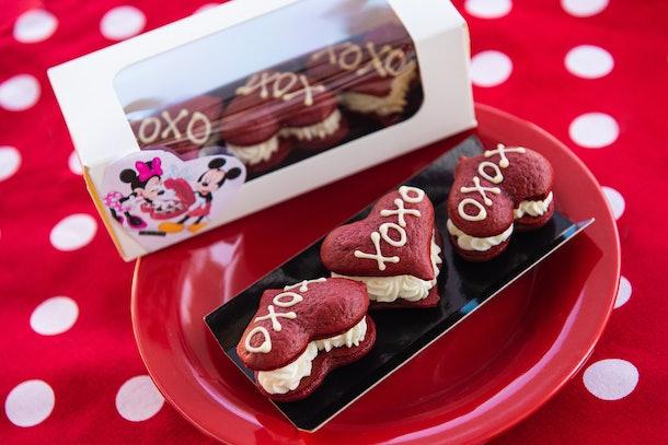"""Trois tartes en forme de whoopie en velours rouge avec """"XOXO"""" écrites dessus sont assises sur une plaque rouge pour la Saint Valentin à Disney."""
