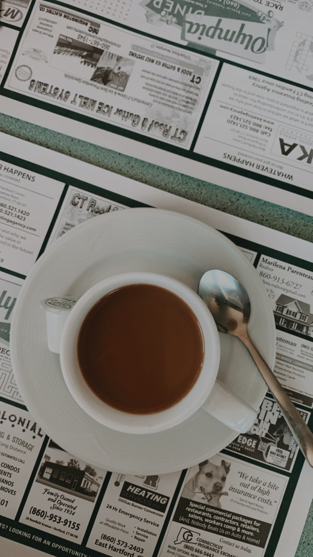 A coffee cup sits on a table in a diner with a spoon next to it.