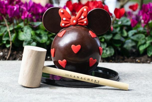 Une piñata au chocolat en forme de Minnie Mouse est assise sur la table avec un maillet en bois pour la Saint Valentin à Disney.