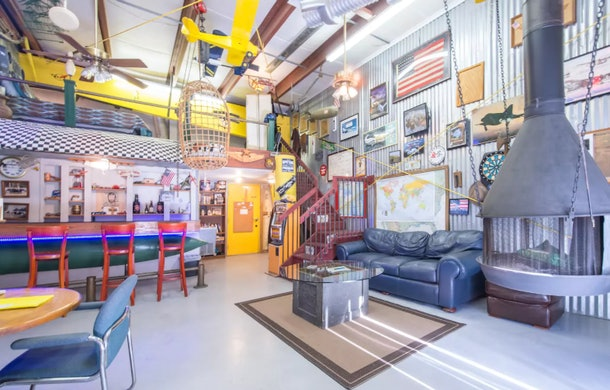 A decorated airplane hangar has pictures of airplanes on the wall and is listed on Airbnb.