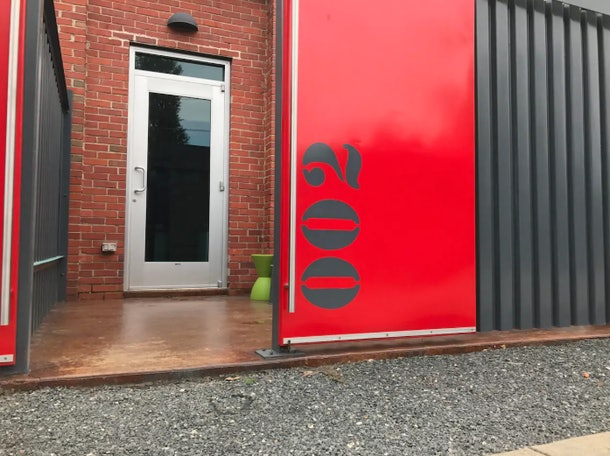 The front door to an apartment in a renovated airplane hangar that's listed on Airbnb is painted red.