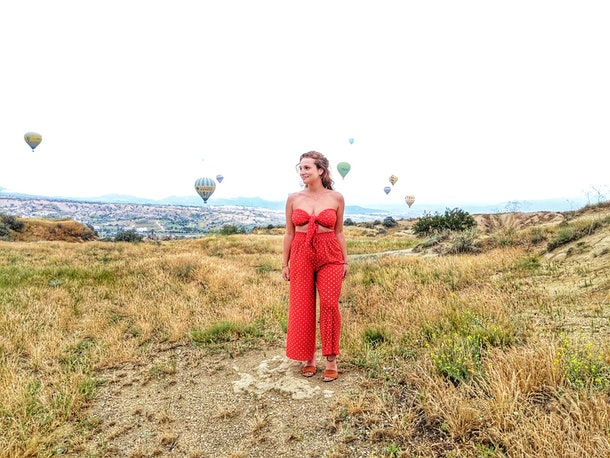 A woman in a bright red jumpsuit smiles and looks off to the side in a field with hot air balloons in the background in Cappadocia, Turkey.