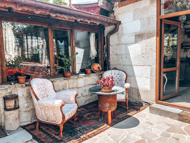 The exterior of the Star Cave Hotel in Cappadocia, Turkey features vintage chairs, a colorful rug, and potted plants.