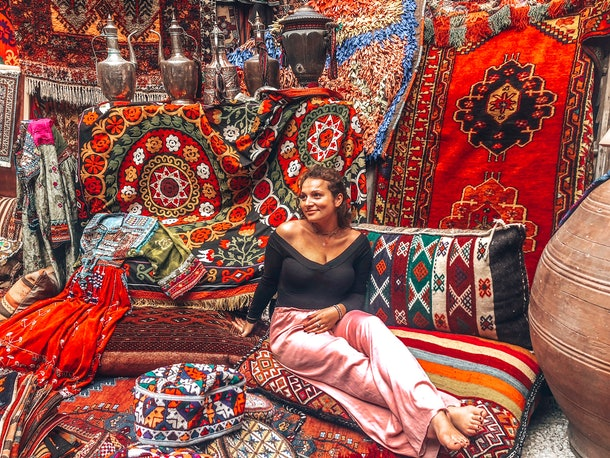 A woman poses on an assortment of colorful rugs and pillows at a rug store in Turkey.
