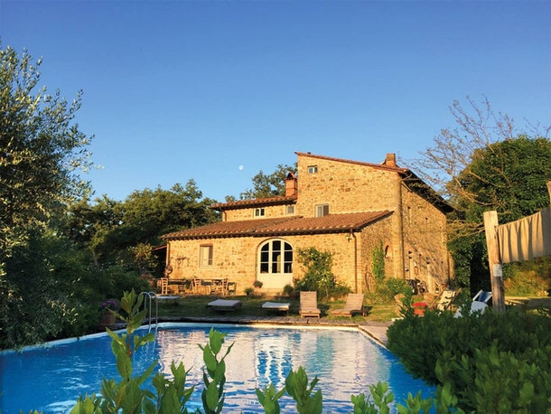 A stunning villa near Florence, Italy has a pool and glows in the midst of golden hour.