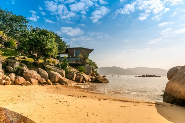 An incredible home in Brazil is nestled right into the rocks of the beach and has a modern design.