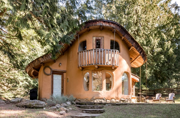 An orange cottage on Mayne Island is tucked into the woods and a short walking distance away from the beach.