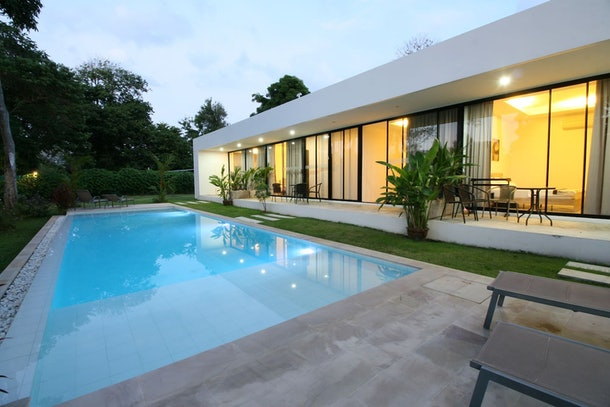 A modern apartment in Phuket, Thailand has a picturesque pool and large windows that overlook a porch.