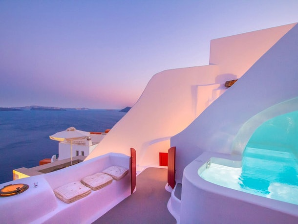 The Hector Cave House in Santorini, Greece glows in purple and pink during a nightly sunset.