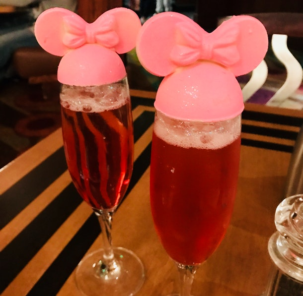 Two pink glittery mimosas with Minnie Mouse toppers are placed on a wood table at The Wave at Disney World' Contemporary Resort.
