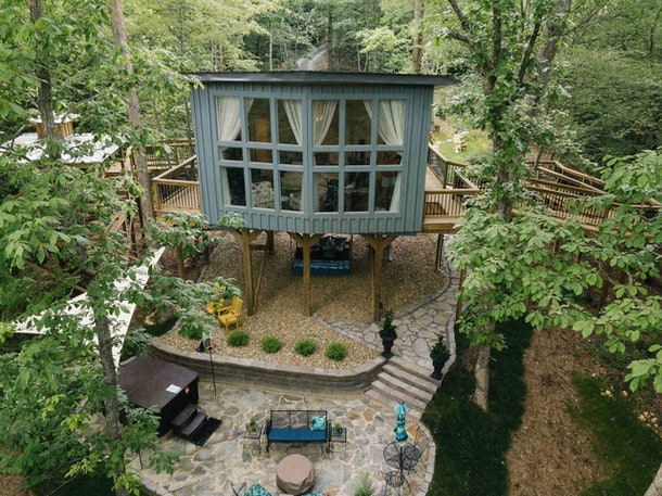 This treehouse in Tennessee has a large window, patio with a hot tub, and is available to rent on Airbnb.