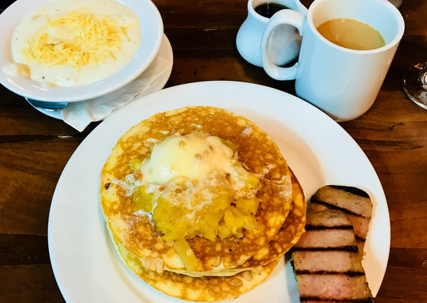 A plate of macadamia nut pancakes with pineapple and spiced ham is placed next to Kona coffee and grits at the Kona Cafe at Disney World.