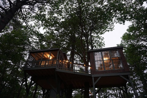 A treehouse that's available on Airbnb in Maine has two rooms and a deck, and is surrounded by trees.