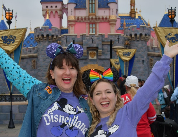 Two friends wearing matching purple Disneyland sweaters and Mickey ears stand in front of the castle with their arms up.