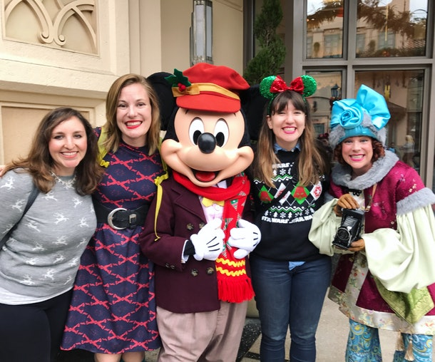 A group of friends pose and smile with Mickey Mouse at Disneyland.