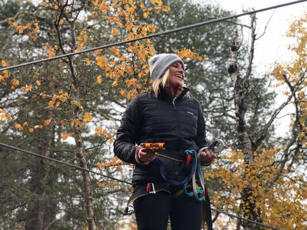 A woman dressed in a gray beanie, black jacket, and black leggings smiles on a fall day while gearing up for zip-lining in Norway.