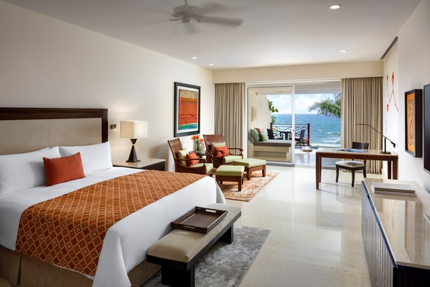 A suite at Grand Velas Riviera Maya features a comfortable bed with orange and red accents, and a balcony with a view of the ocean.