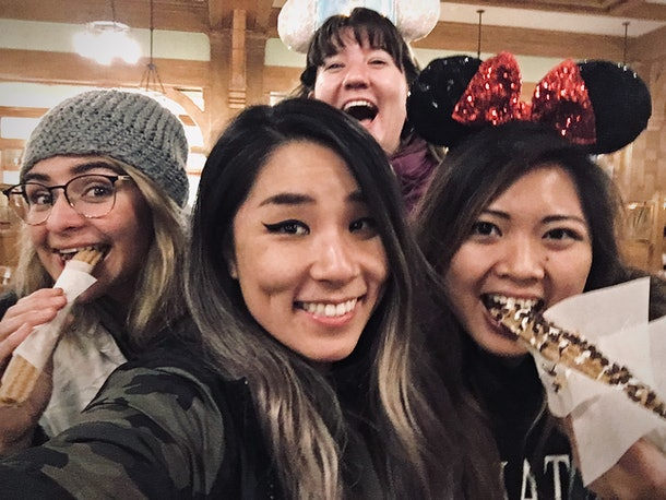 A big group of friends huddle together to snap a selfie with churros at Disneyland
