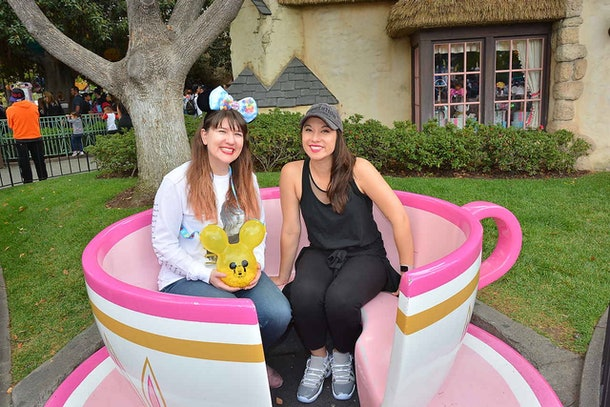 "Two happy women sit in a pink tea cup at Disneyland from ""Alice in Wonderland.'"