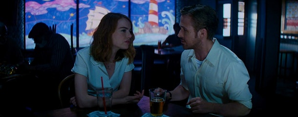 Ryan Gosling and Emma Stone sit in a jazz club during a scene in 'La La Land.'