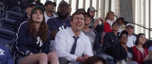 Zoey Deutch and Glen Powell sit in the stands of Yankee Stadium during a scene in 'Set It Up.'