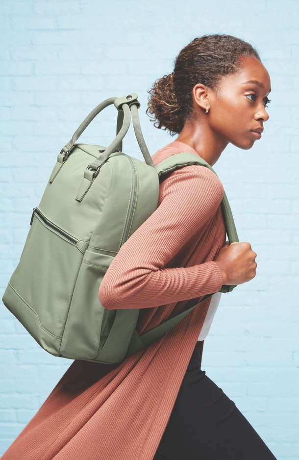 A woman carries a green backpack from Target's Open Story luggage brand.